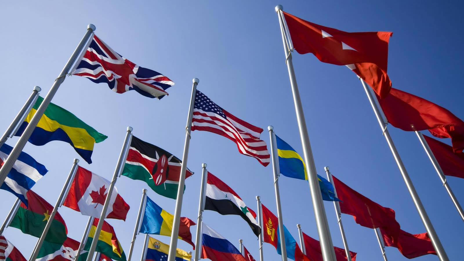 Multiple international flags flying against blue sky
