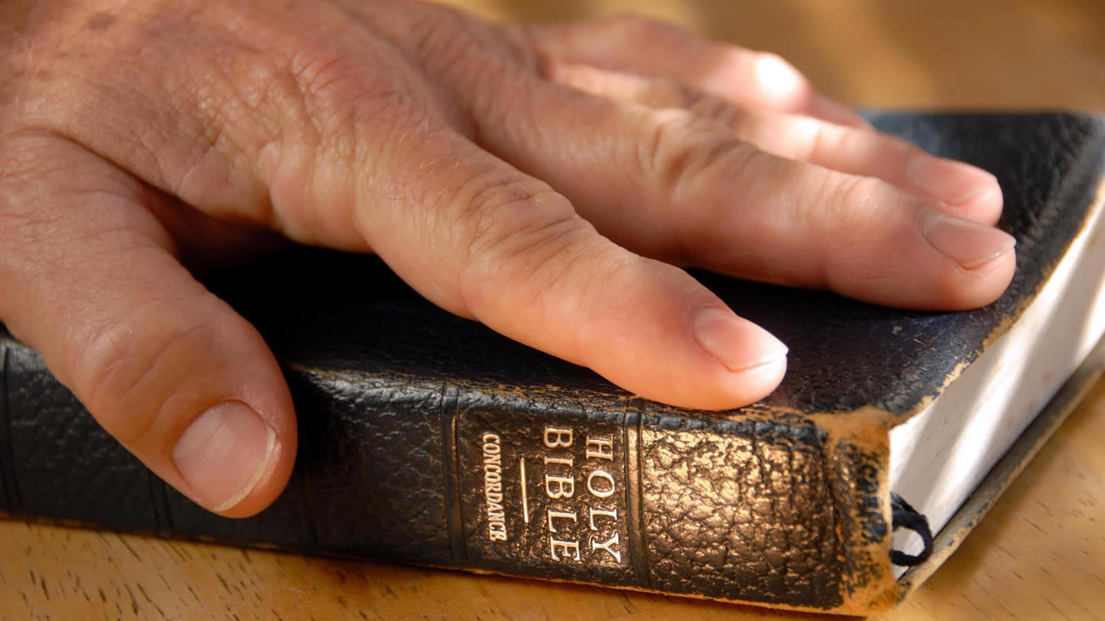 Hand on Bible on Table