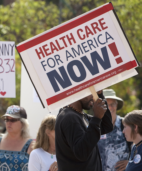 """A man holds a sign reading """"Health Care for America Now"""""""