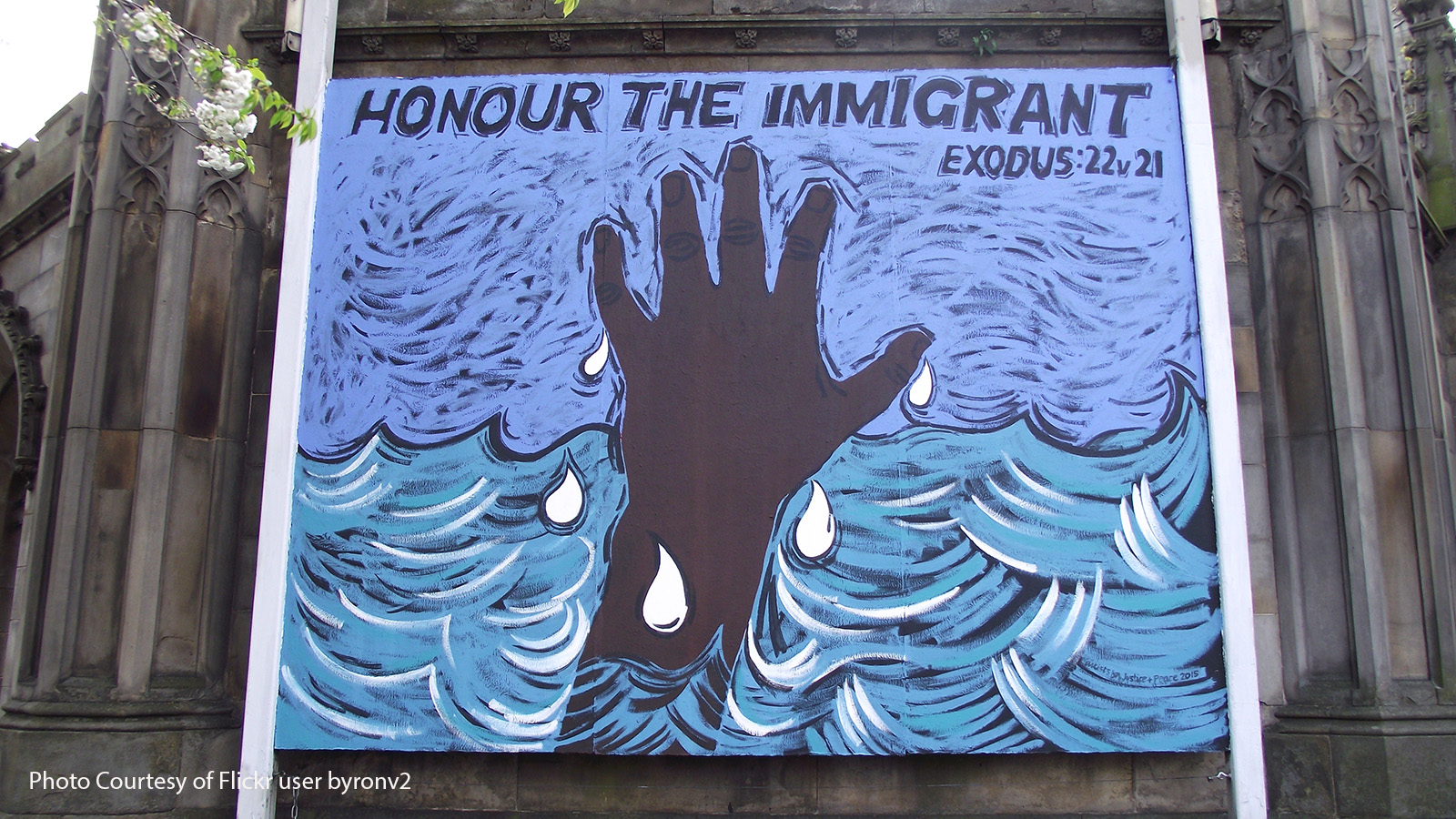 'Honour the Immigrant' mural on the side of a church.