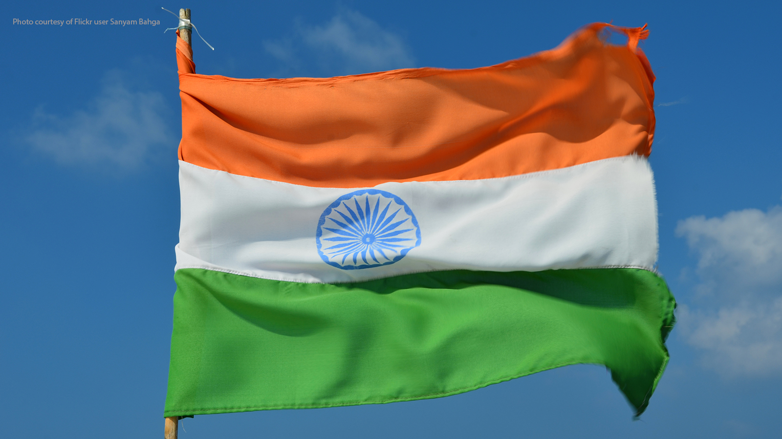 Indian flag against blue sky.