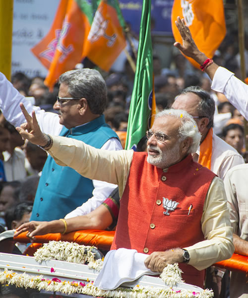 Narendra Modi waving to crowd during parade in India