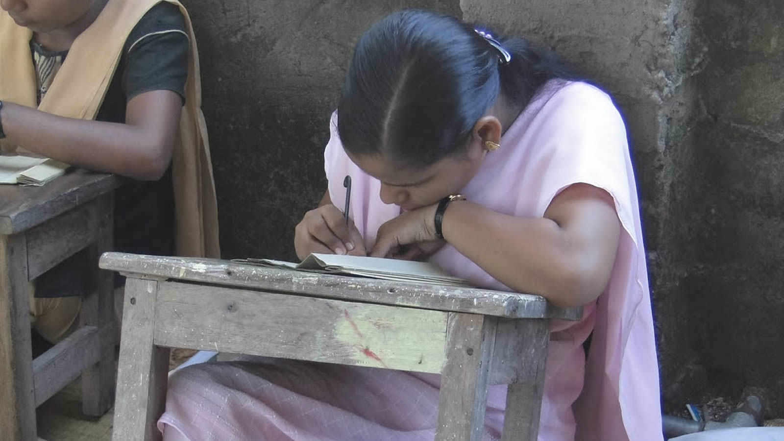 Indian Woman in Pink Writing on Desk