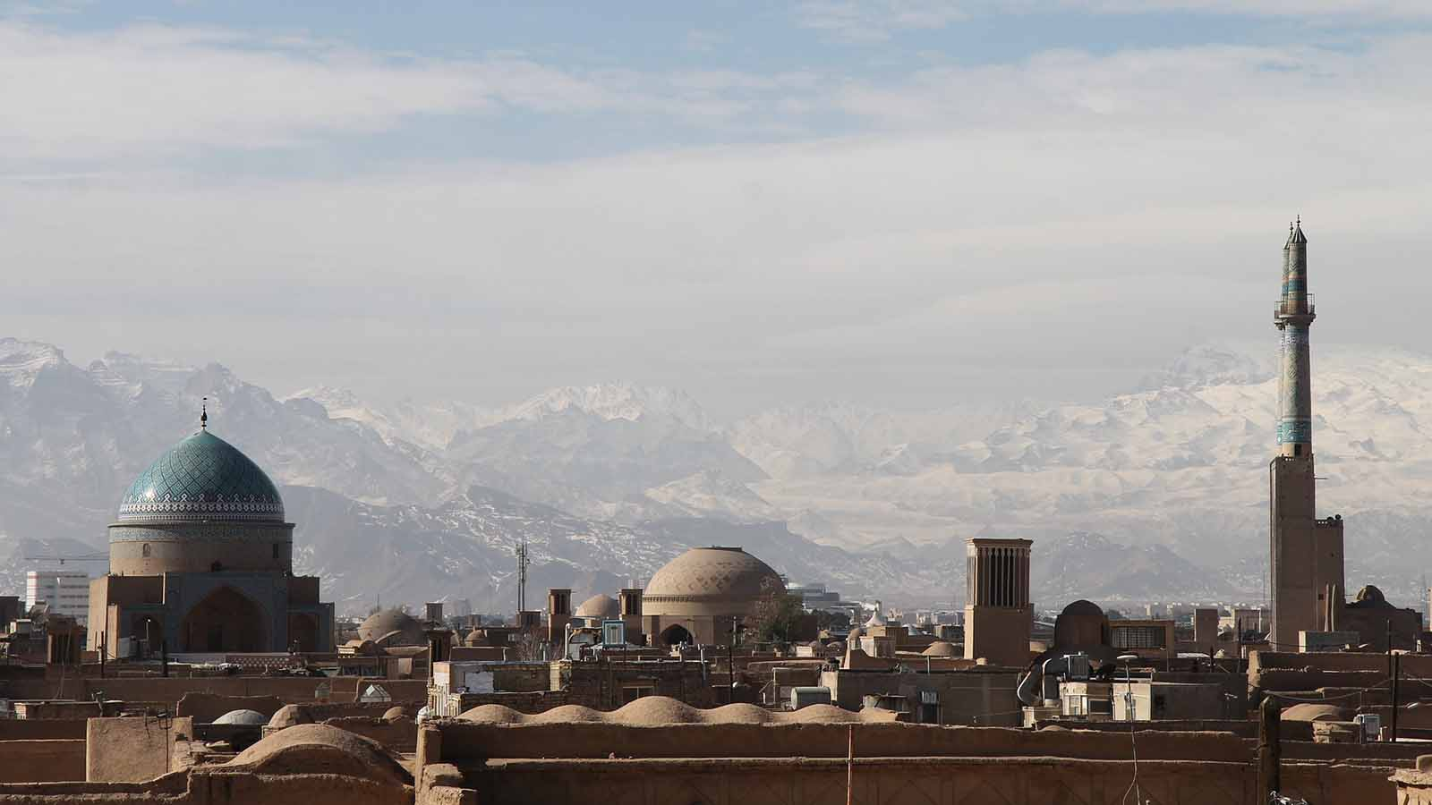 Iranian buildings and mosques with mountains in the horizon.