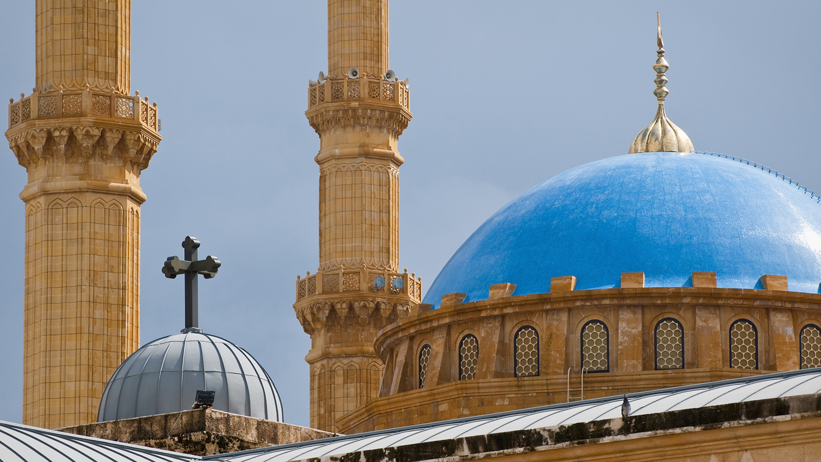 Church dome with cross in front of a mosque with a blue roof in Beirut, Lebanon