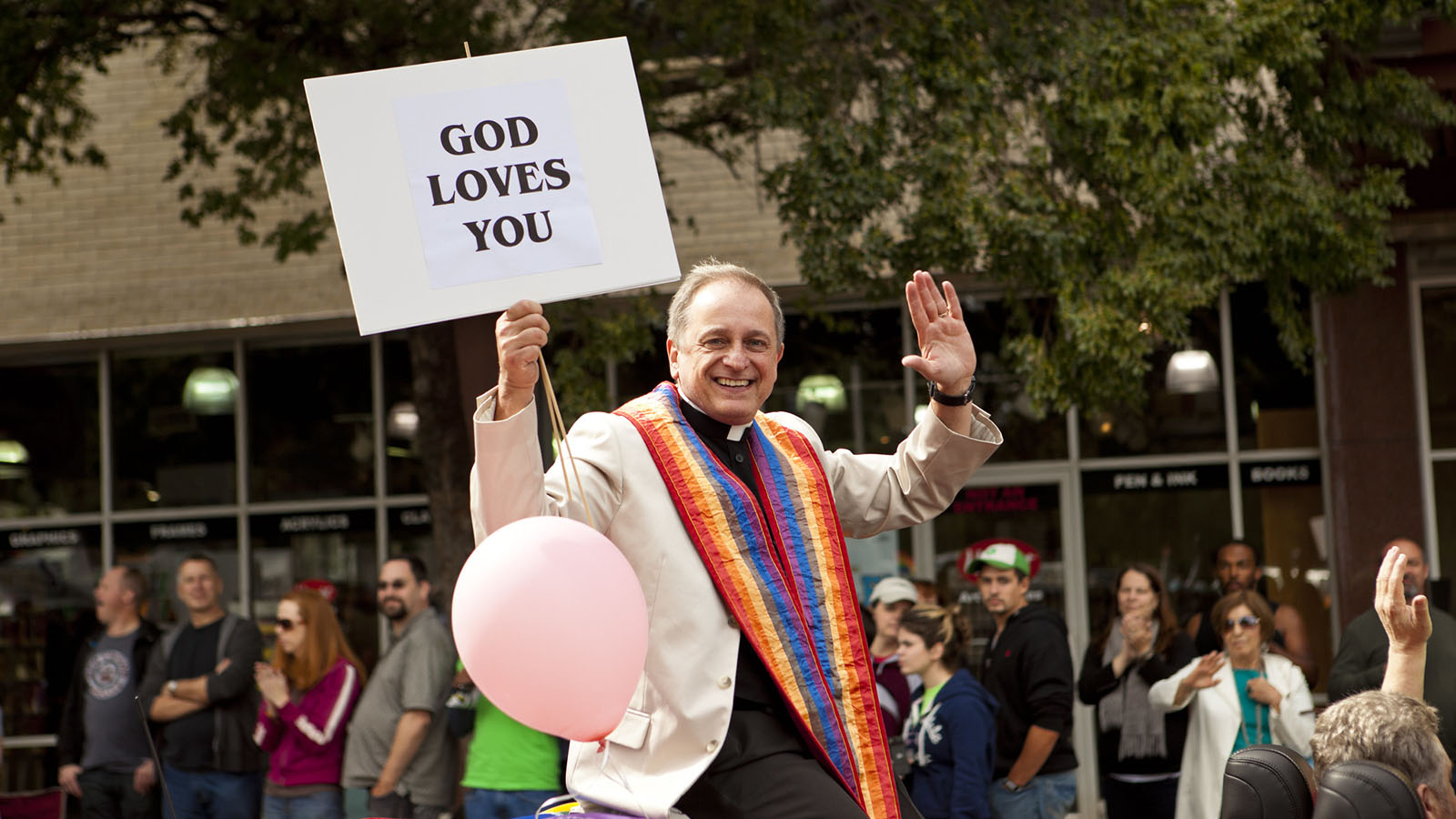 A man in a parade holds a 'God Loves You' sign