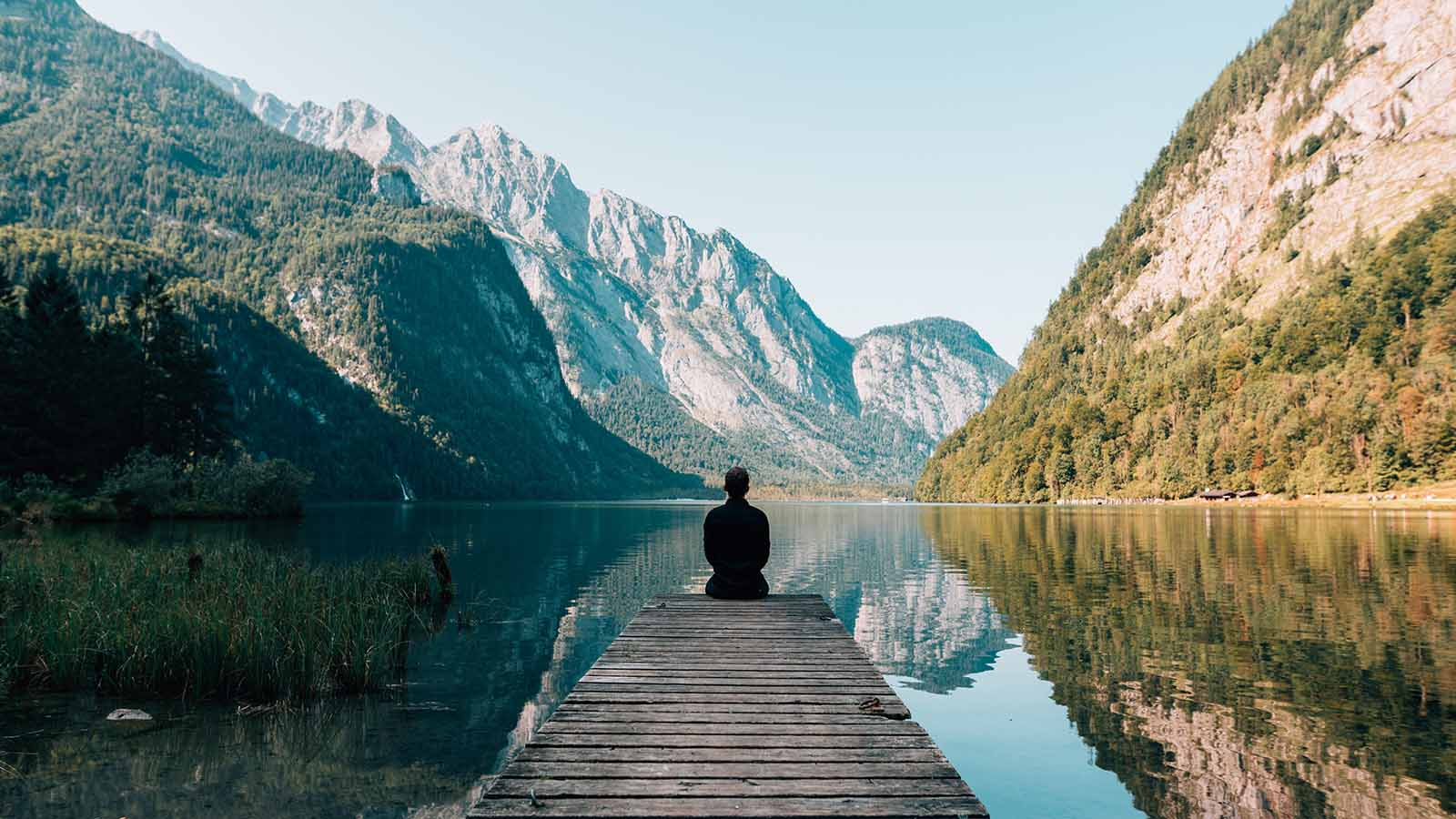 Man looking reflective over lake and mountains landscape.