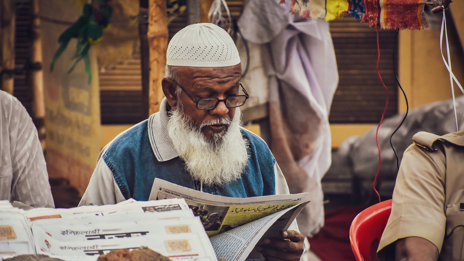 Religious man reading a newspaper in the market.