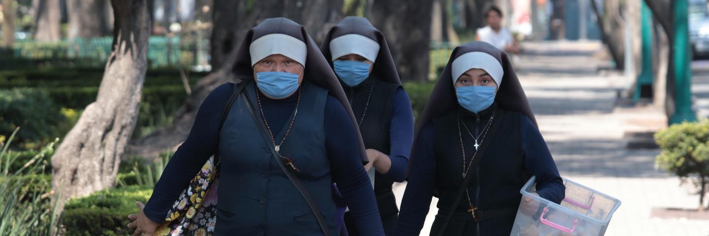 A group of three nuns wearing masks