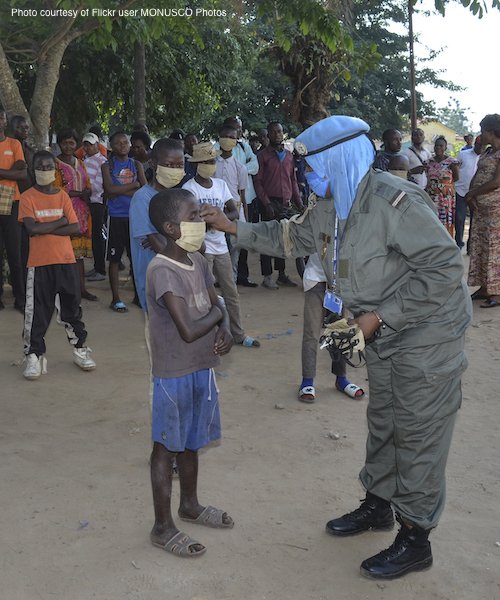 Masked peacekeeper with child in the Democratic Republic of Congo