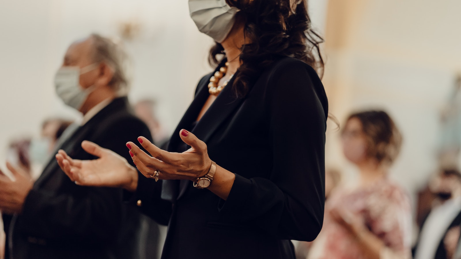 Masked woman with hands up in a worship setting
