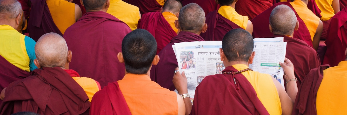 Monk in saffron robes reading a newspaper in a crowd of co-religionists