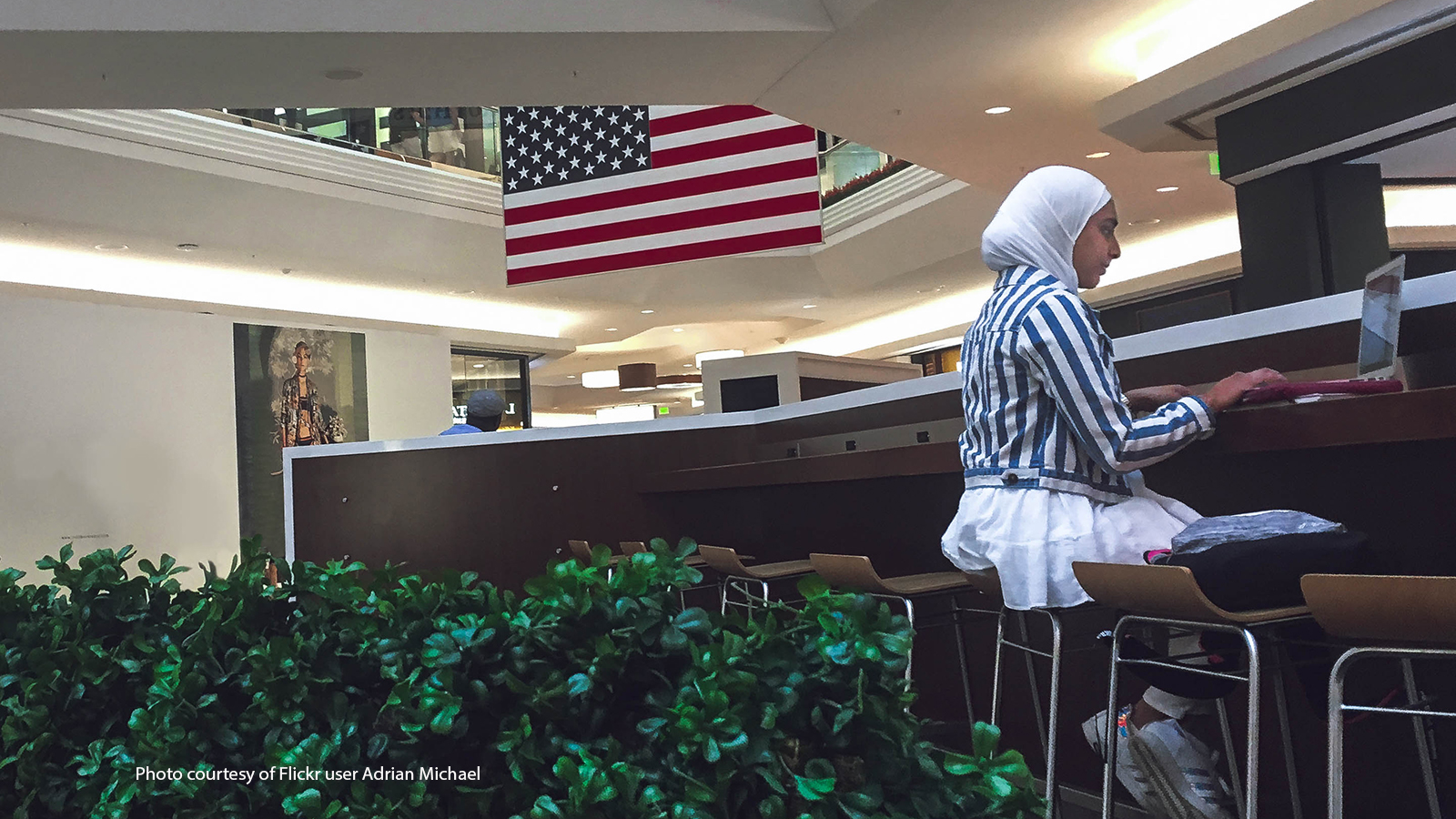 Muslim girl working on a laptop with American flag behind her.