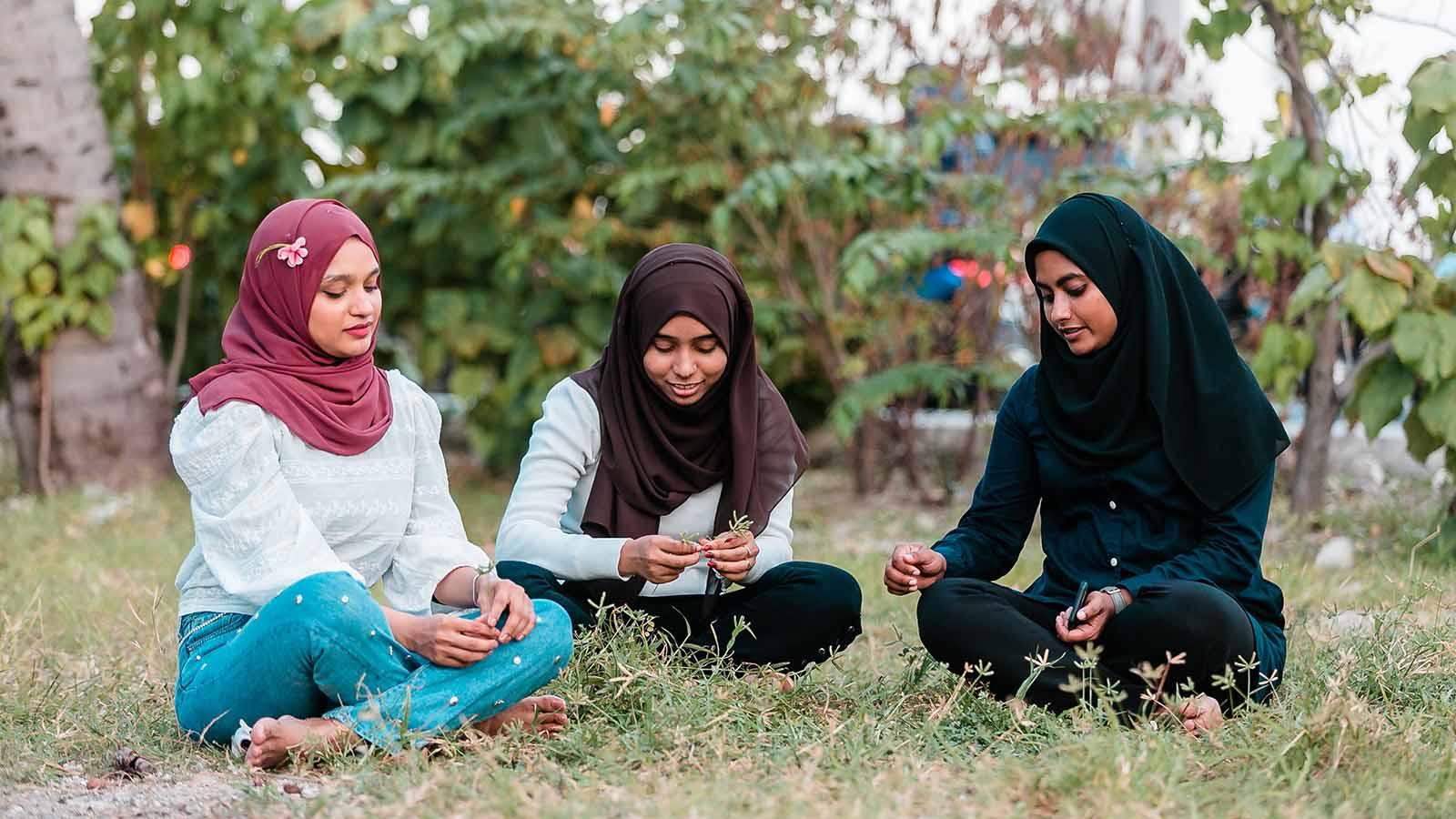 Muslim girls sitting in a field.