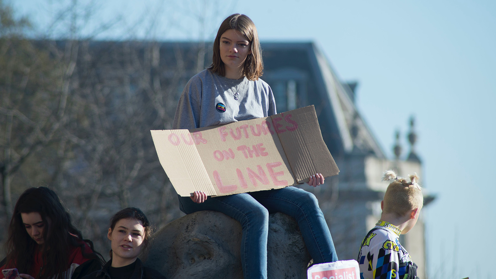 """Girl holding a sign that says """"Our Futures On The Line"""" at a protest."""