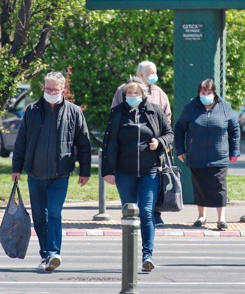 People wearing masks walk outside