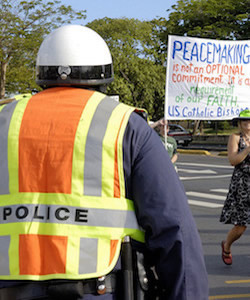 Policeprotestcatholicpeacemakingsign