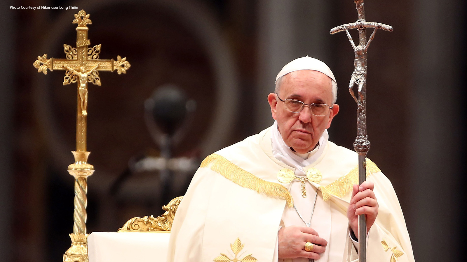 Pope Francis standing, somber, with crosses.