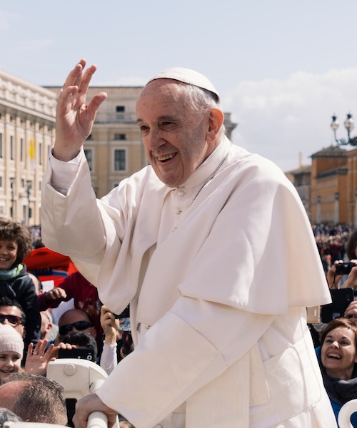 Pope Francis greets a crowd of people outside the Vatican