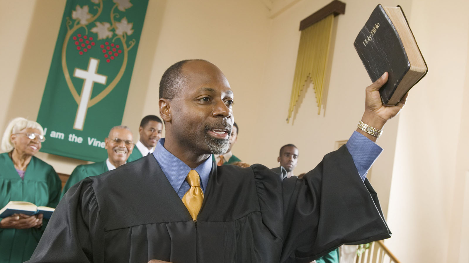 A preacher preaches the gospel while holding a bible. Members of the chorus read and smile in the background.