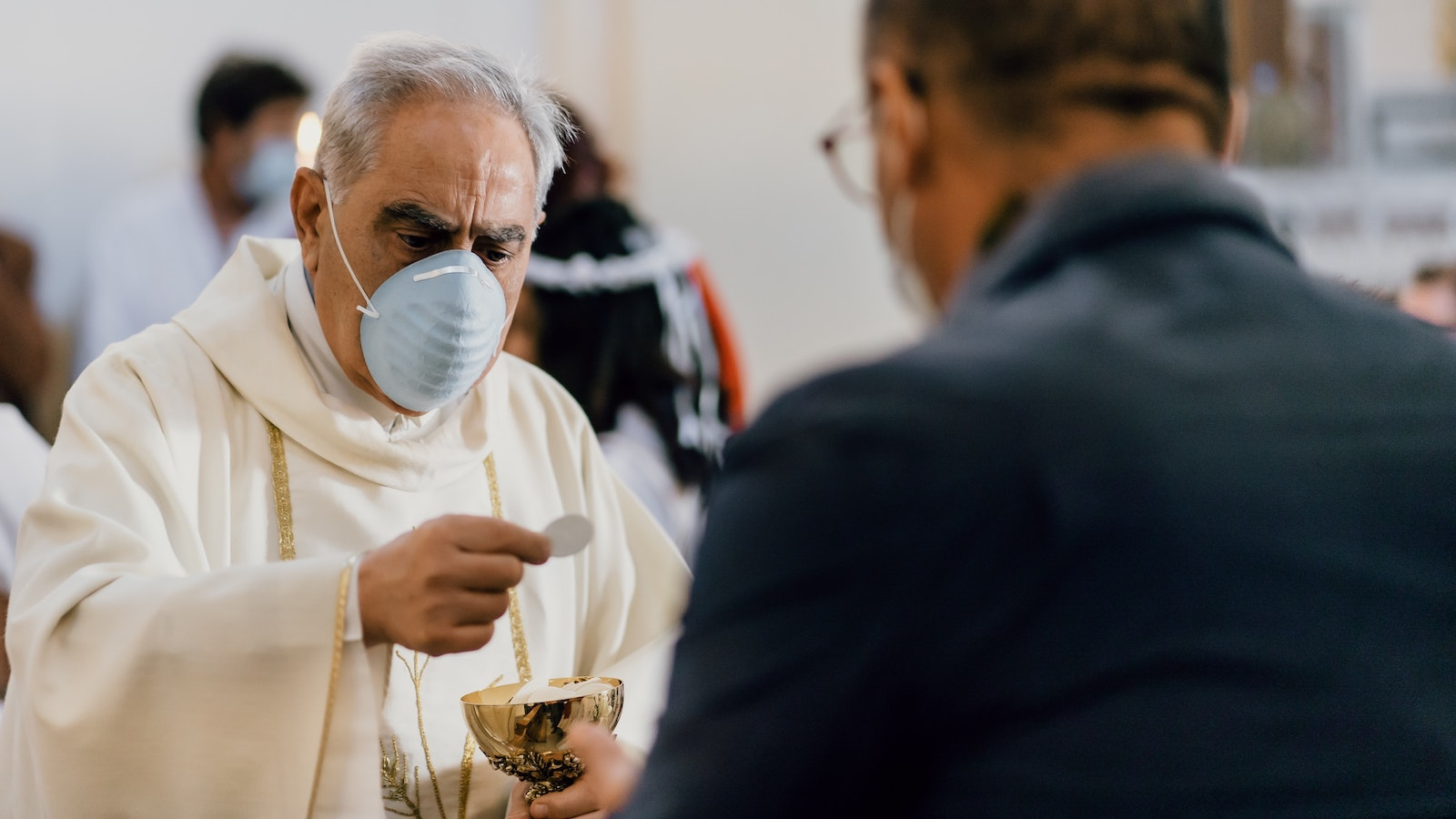 Masked priest delivers Communion