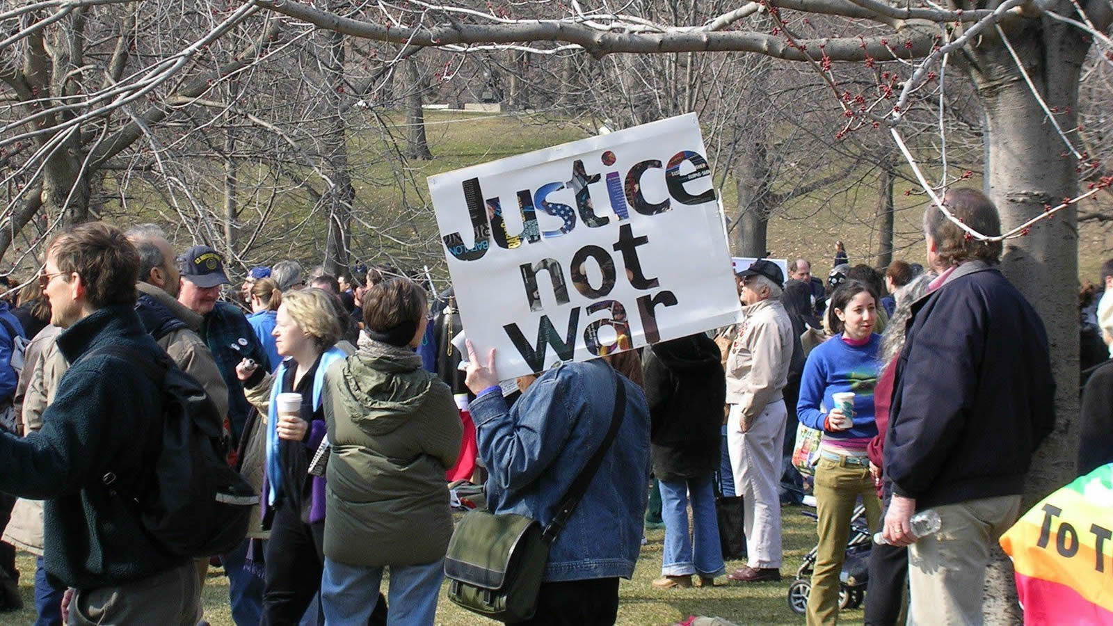 """Protesters in Park with """"Justice Not War"""" Sign"""