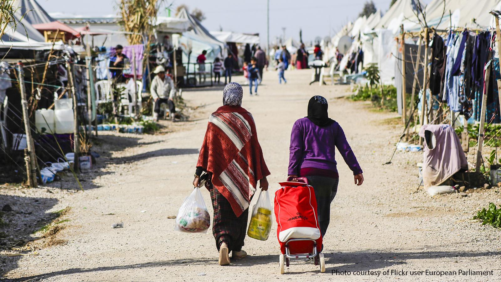 Two Syrian women walking through a refugee camp in Turkey.