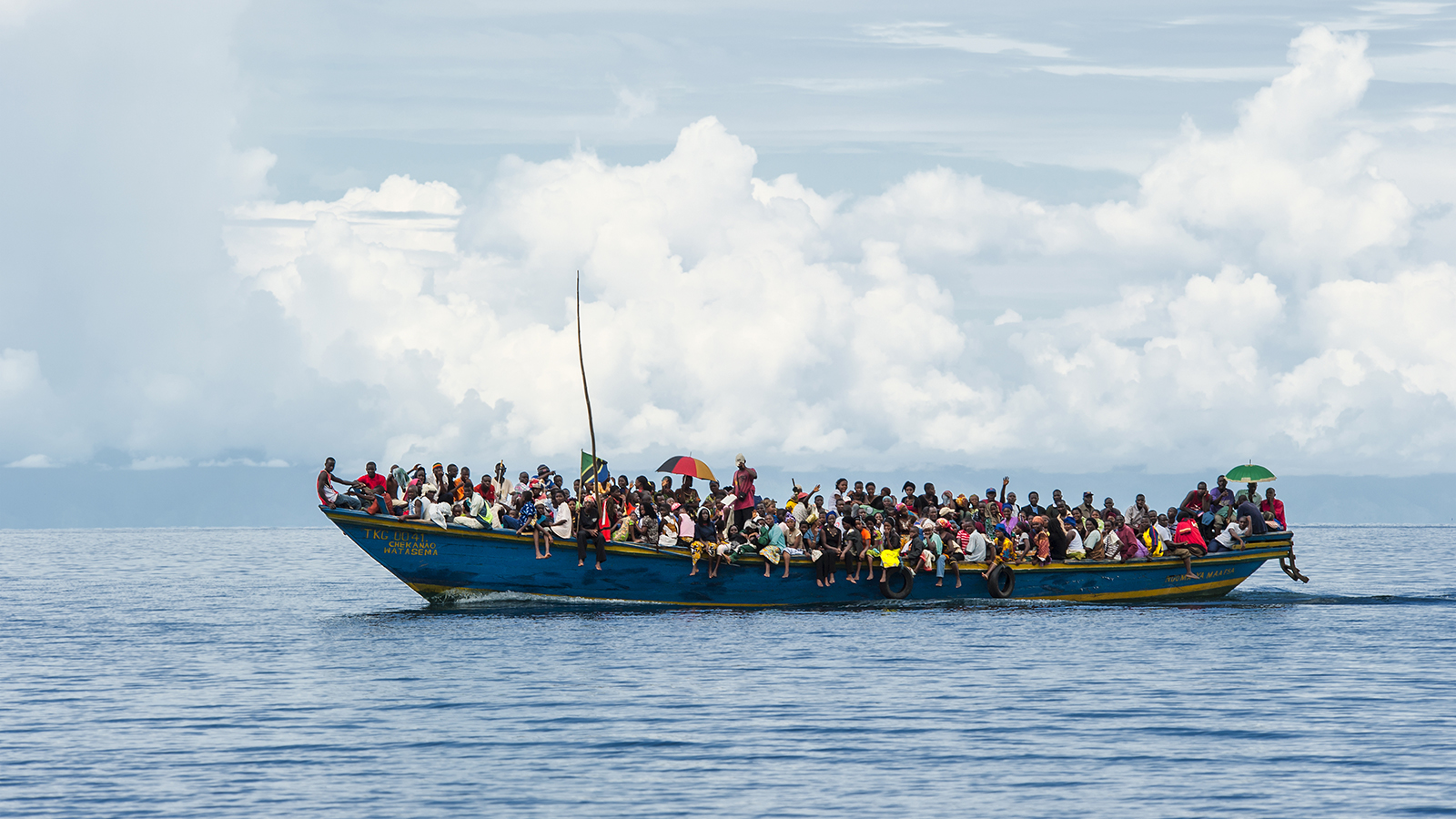 Wooden boat packed with refugees on the water