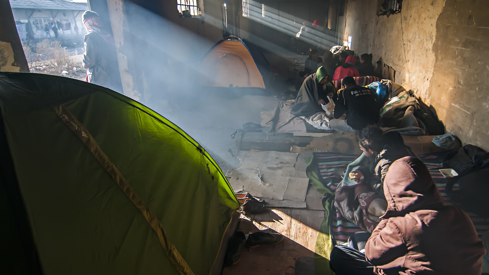 Refugees eating in tents and abandoned building in winter.