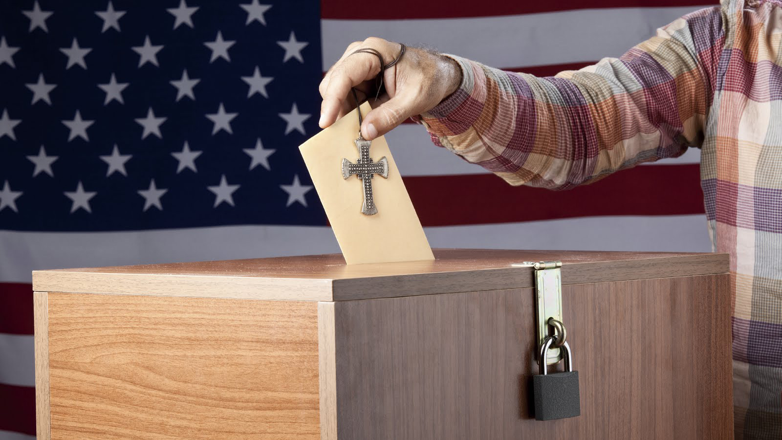 Many voting with a cross, in front of a U.S. flag.