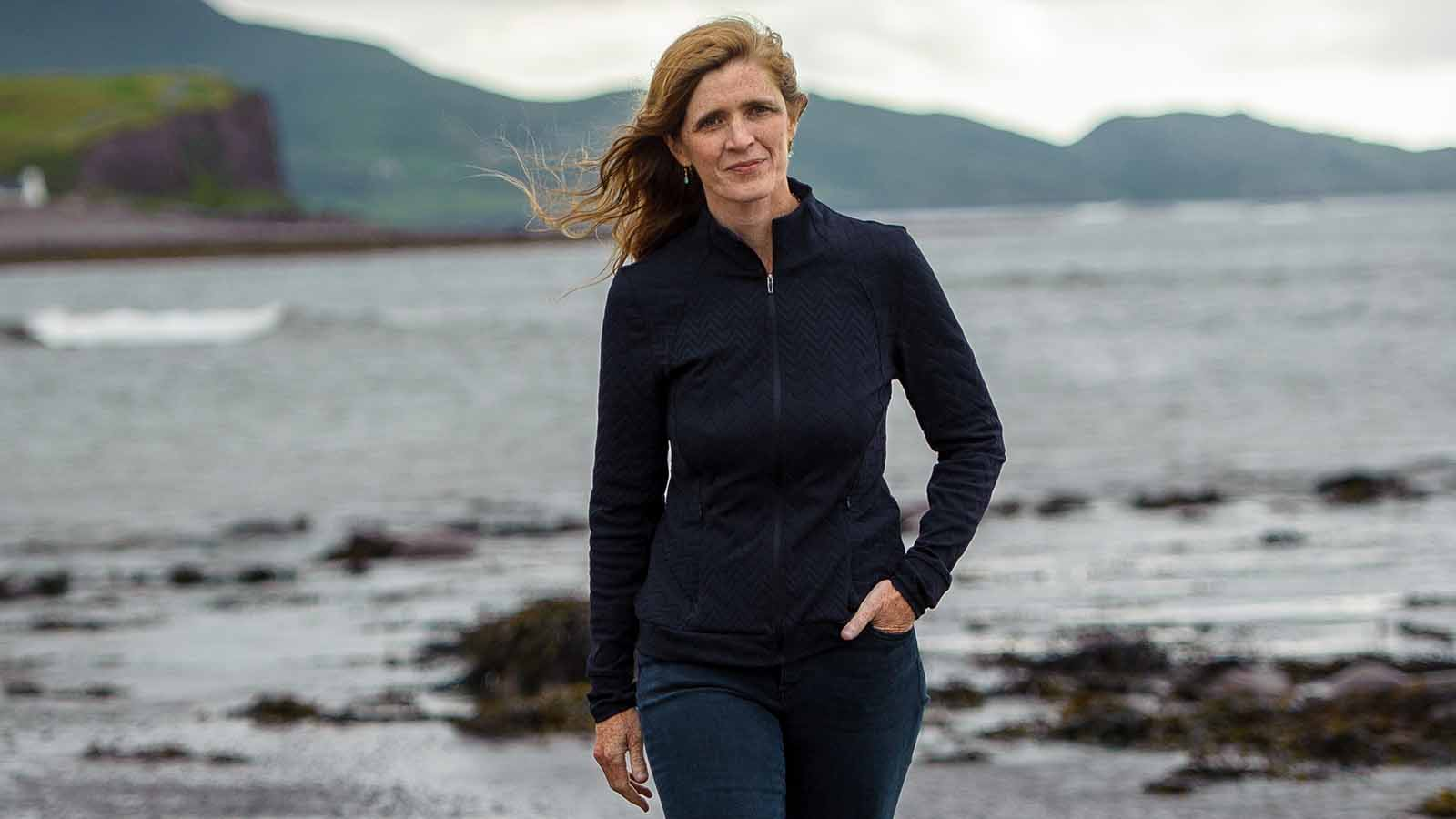 Amb. Samantha Power with an ocean and mountain landscape background.
