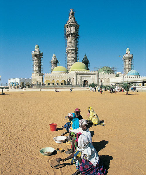 People sitting in the sand in front of a Senegalese mosque under construction