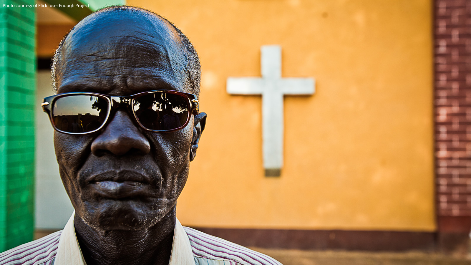Man with sunglasses in front of a wall with a cross in Abyei, Sudan