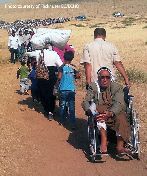 Syrian Kurdish refugees walking in a line into Turkey in 2014