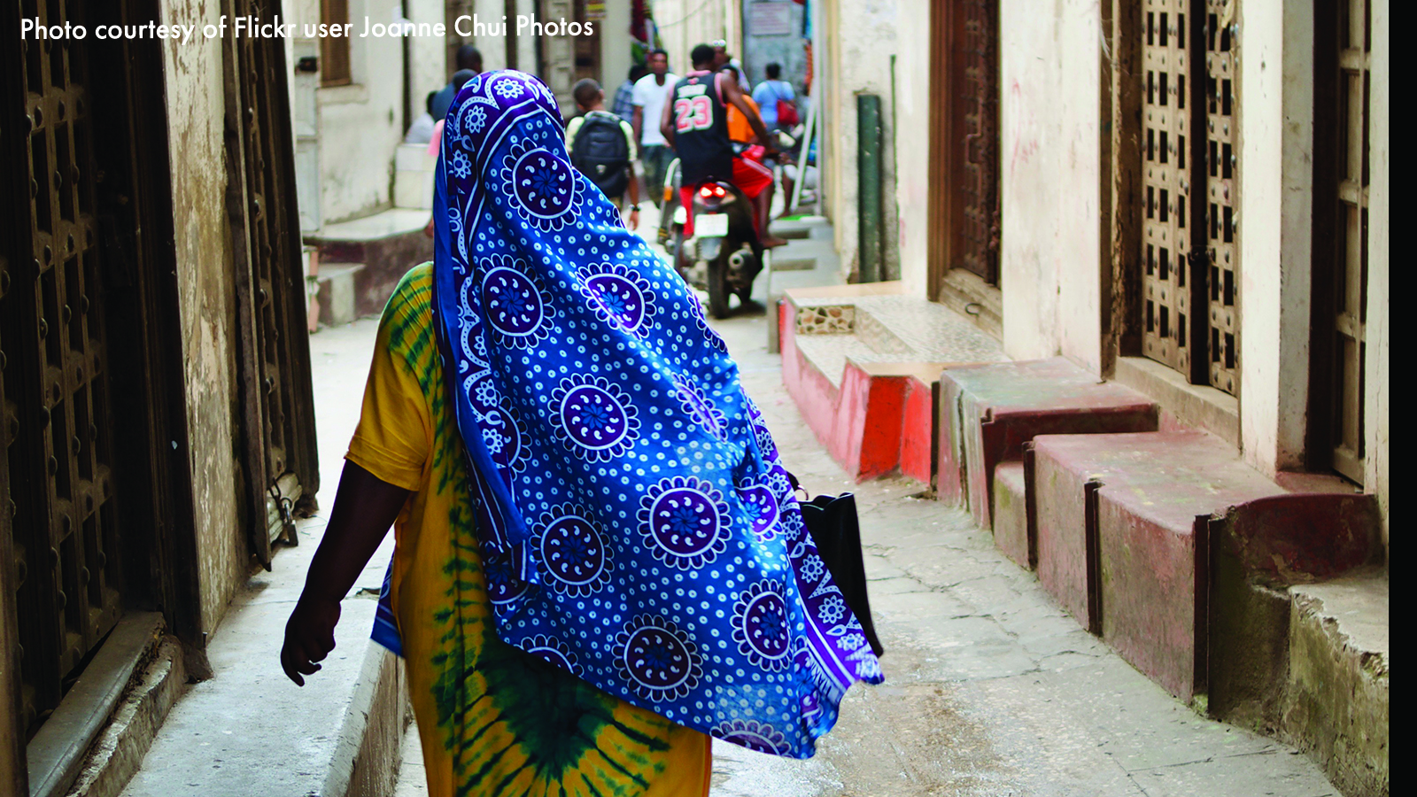 Tanzanian woman in blue headscarf and yellow dress walking down the street