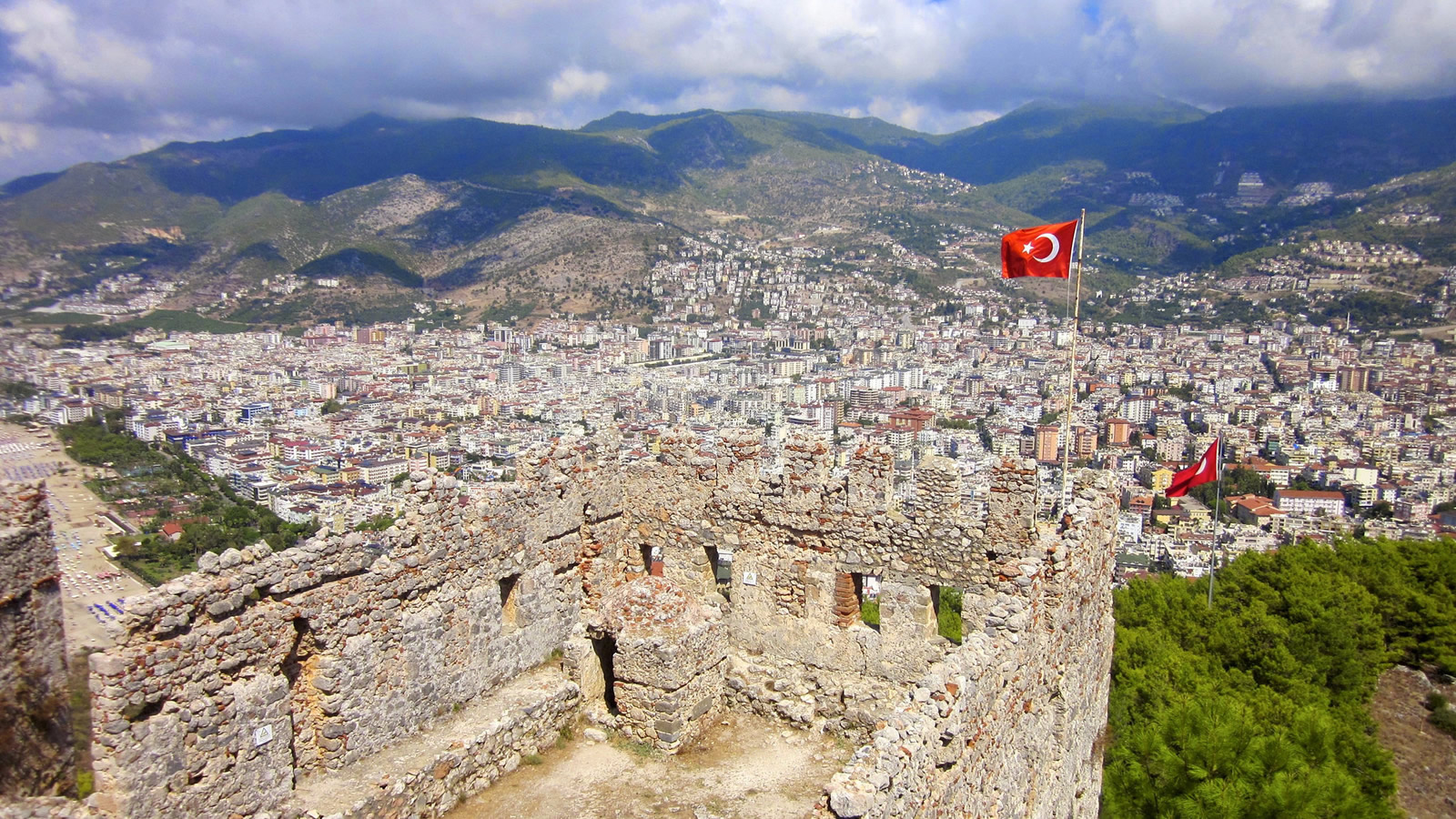 Turkish flag on old ruins, with a modern city in the background.