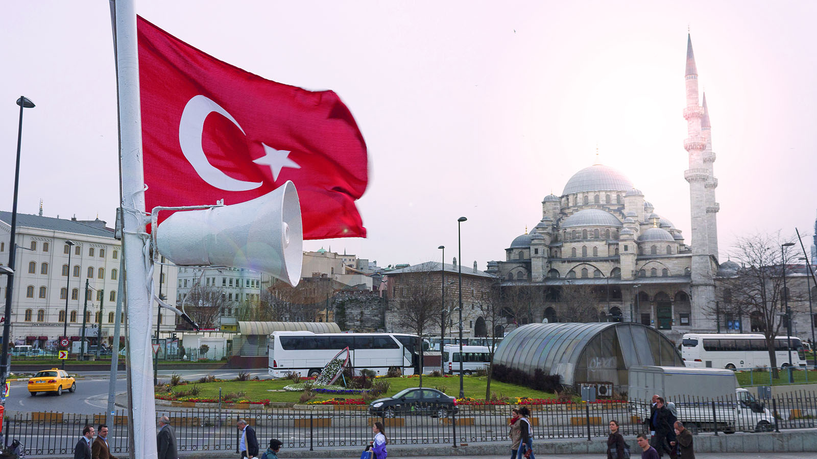 Turkish flag and bullhorn on pole in front of a mosque