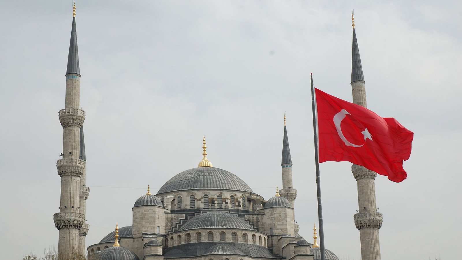 Turkish flag flies in front of the Blue Mosque in Istanbul, Turkey
