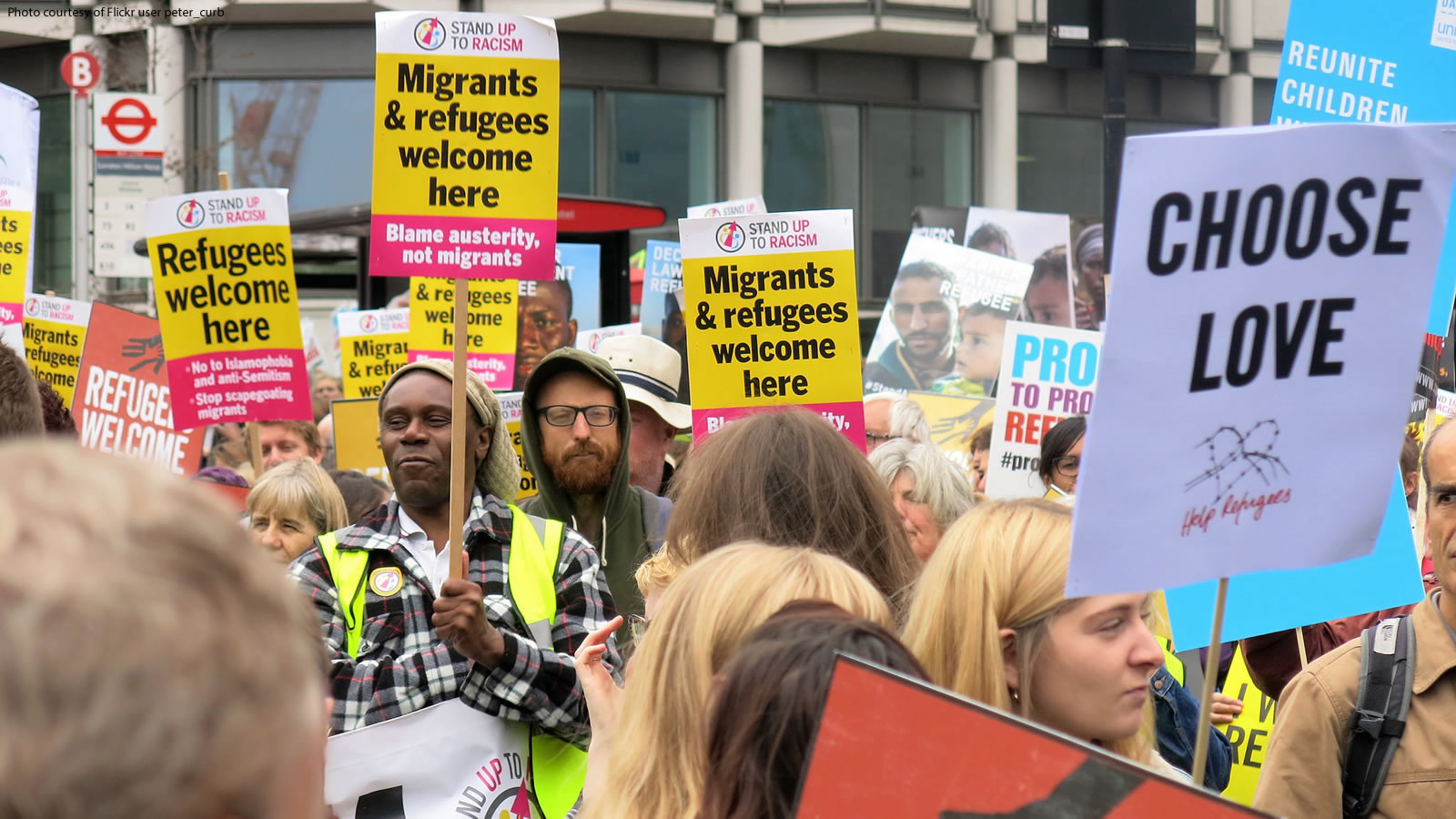 "Individuals holding ""Migrants and Refugees Welcome Here"" signs in the United Kingdom."