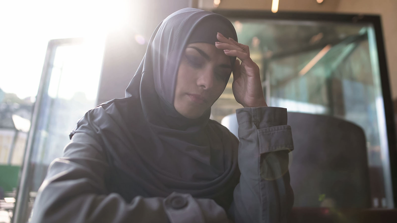 A woman wearing a hijab looks pensive while holding her temple and closing her eyes.
