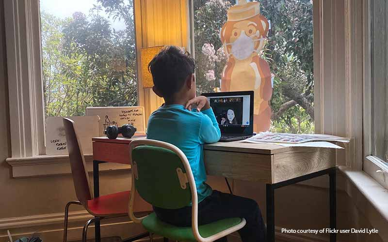 Young boy attends class virtually due to COVID-19 restrictions.
