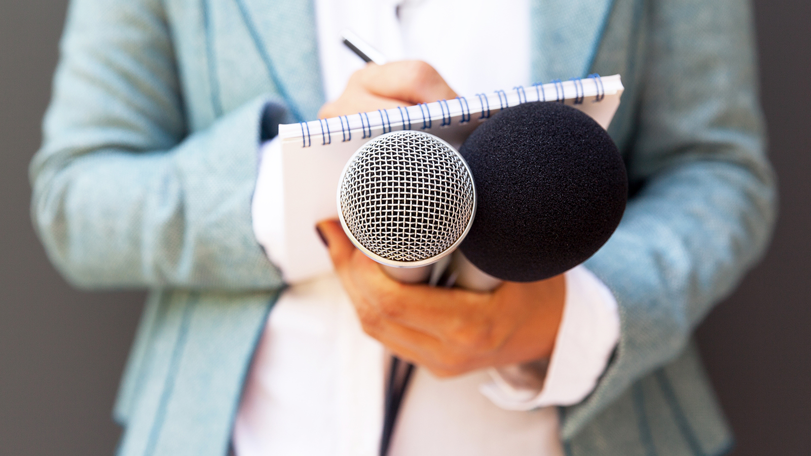 Woman reporter holding a notebook and microphones
