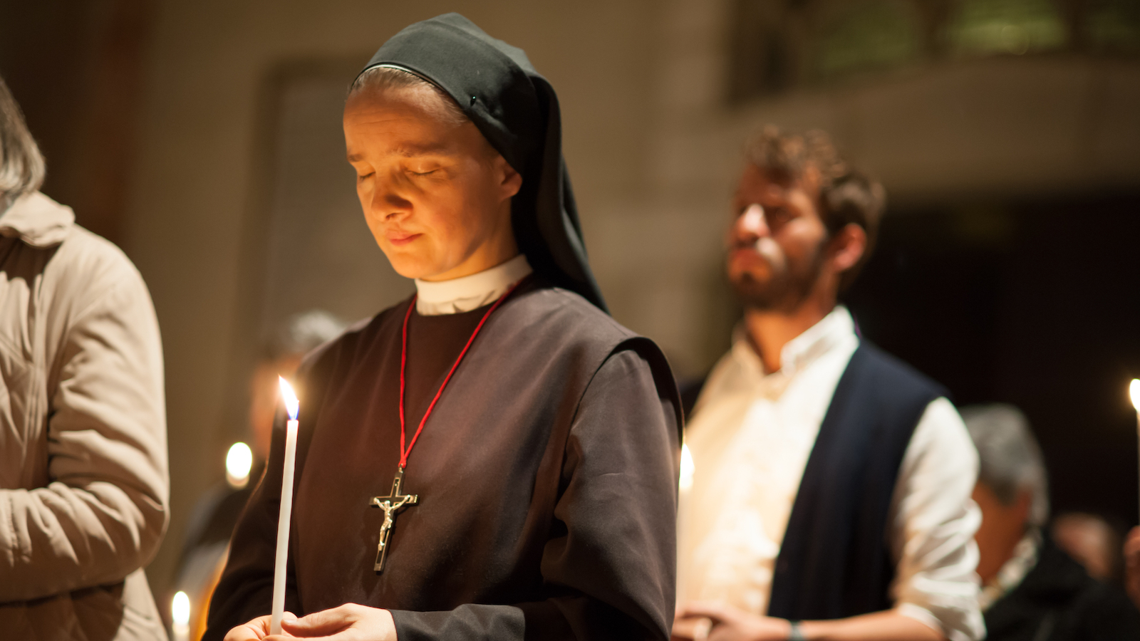 Nun holds a candle while praying in a church