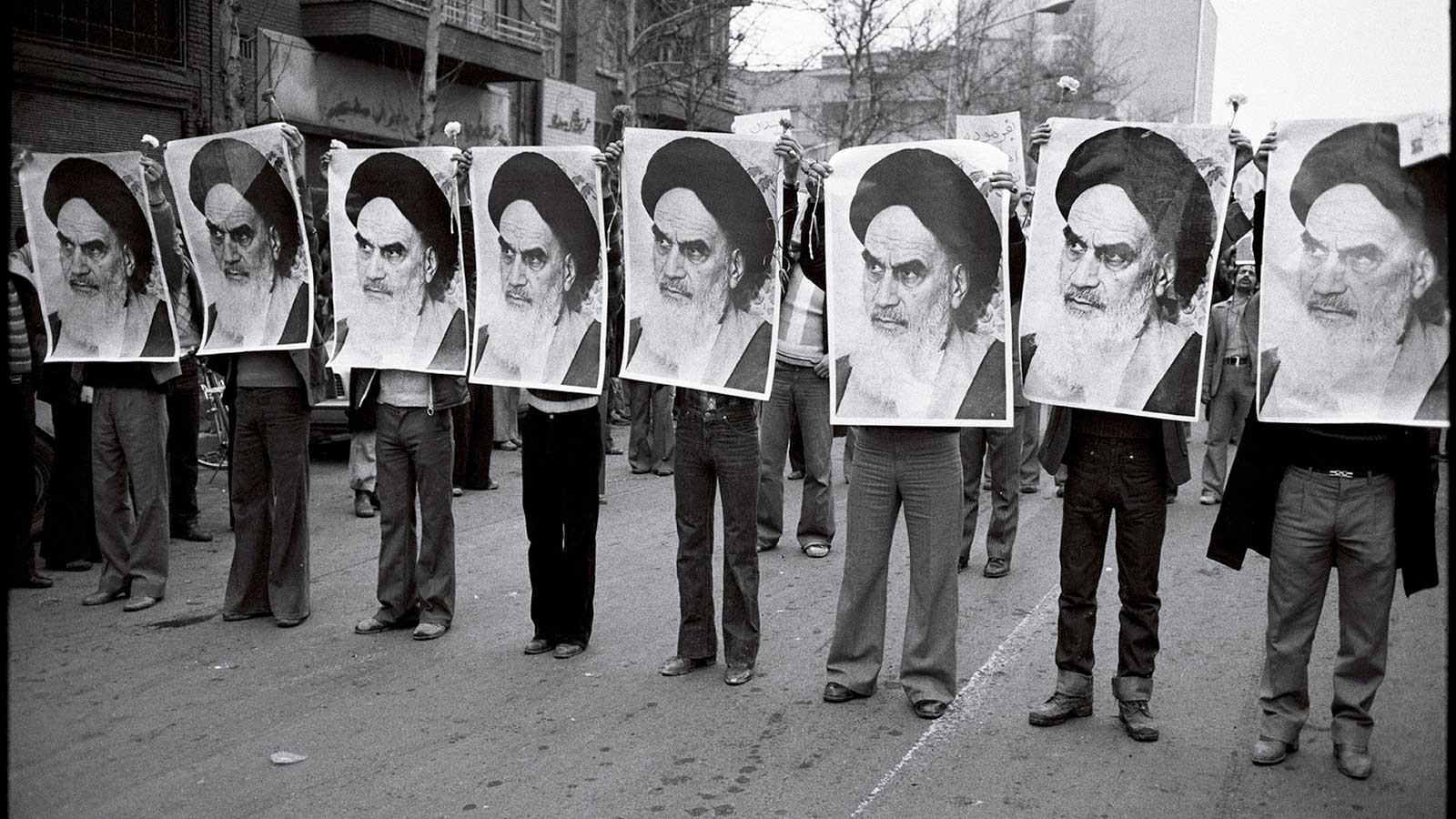 Row of men holding Khomeini's photo as part of a protest linked to the Iranian Revolution.