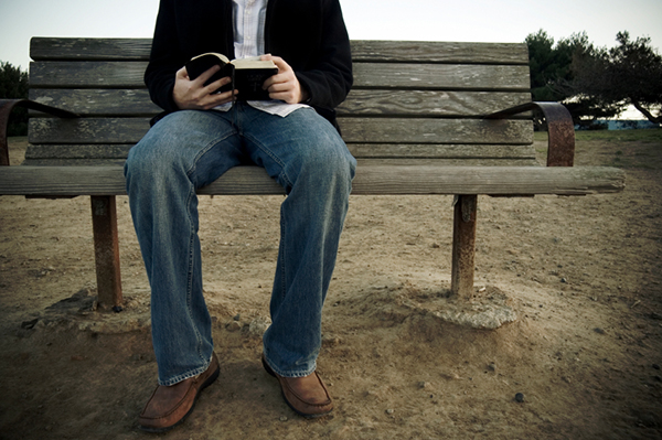 A photo of a man sitting on a bench reading the Bible