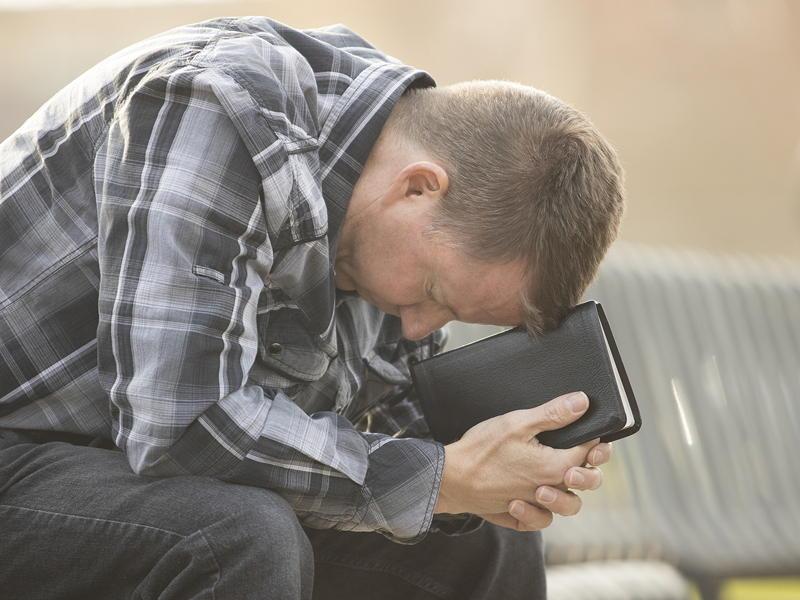 Man praying with Bible illustration