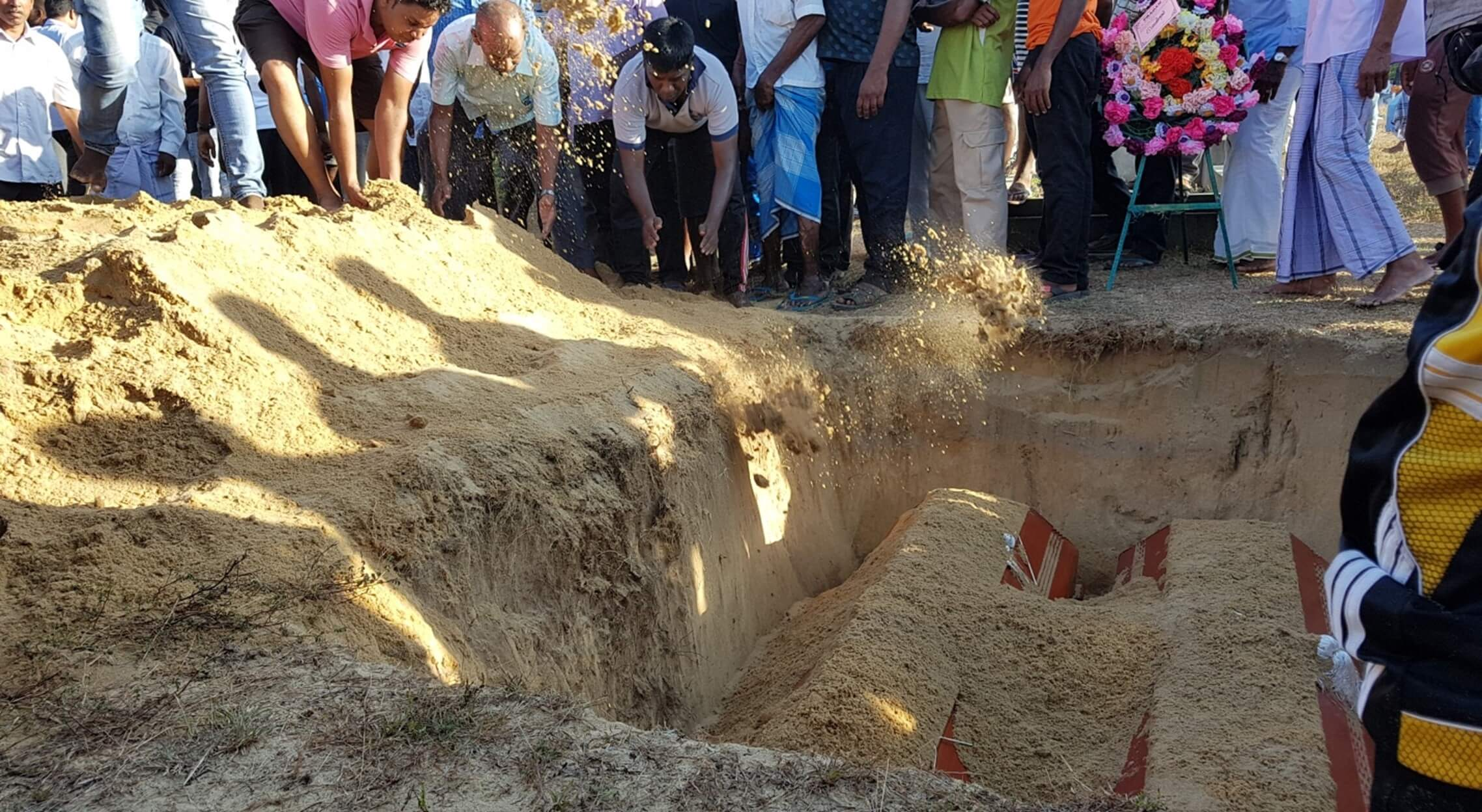 Photo of the burying of coffins for a Sunday school teacher and 13-year-old boy who died in the Sri Lanka church suicide bombings
