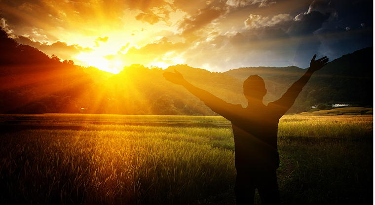 Man with outstretched arms toward sun illustrating praise