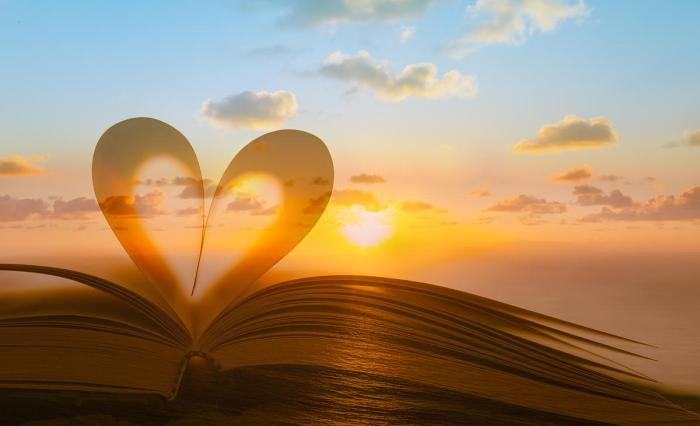 Image of Bible pages bent in the shape of a heart with a sunset behind them