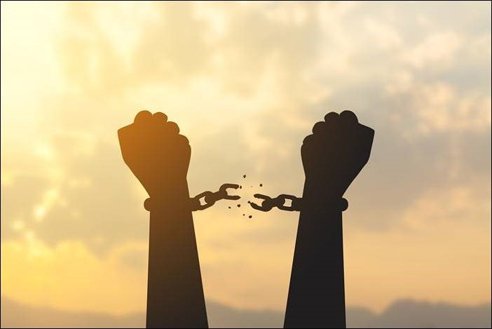 Illustration of upraised hands breaking free from chains